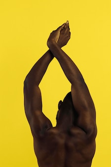 Back view african american man stretching next to illuminating wall