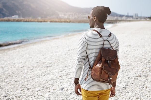 Back view of african backpacker facing sea in trendy clothes, traveling alone in european summer resort town, admiring sky-blue water and mountains, thinking about something secret and intimate