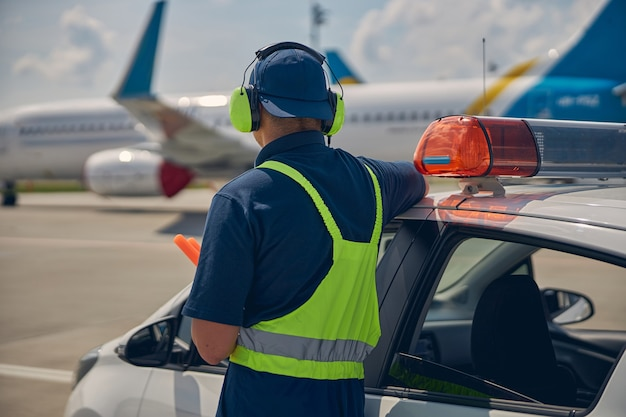 Back view of an aircraft marshaller in headphones and the safety overalls standing by the car