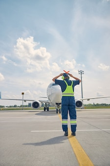 Back view of an aircraft marshaller making the emergency stop signal to the airplane crew