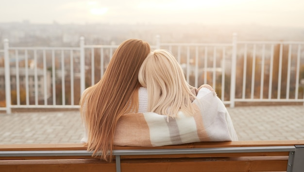 Back view of anonymous girlfriends wrapping in warm scarf and embracing each other while resting on bench on autumn day on observation platform