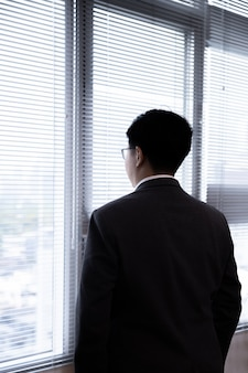 Back view of asian businessman in a suit looking through office window with blank copyspace