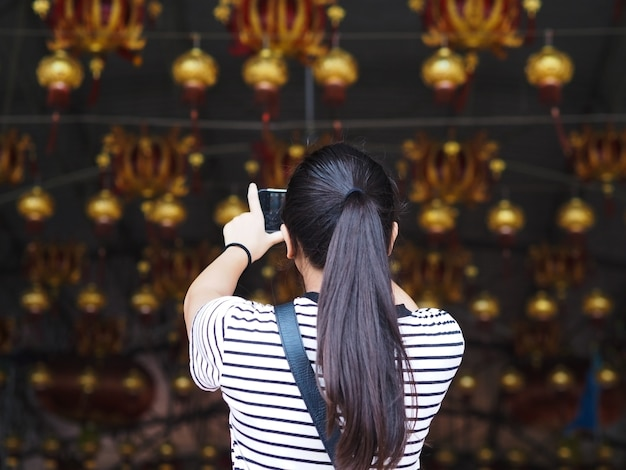 Back view of asian girl taking photograph the lamp from mobile phone at china shrine