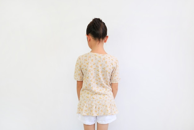 Back view of asian little girl with bun hair up on white