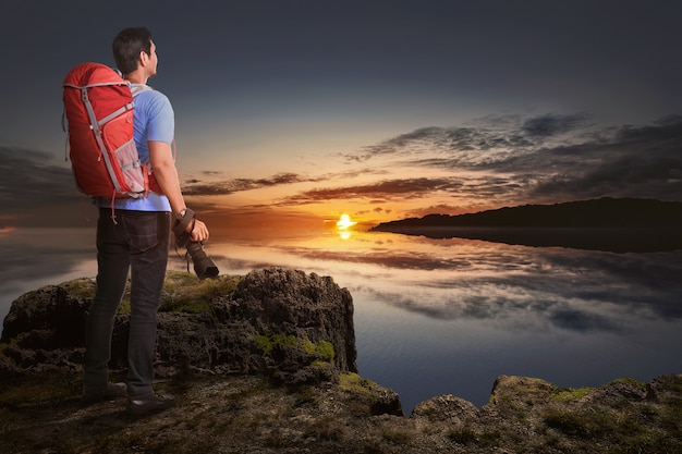 Back view of asian tourist man with camera and backpack looking at sunset view