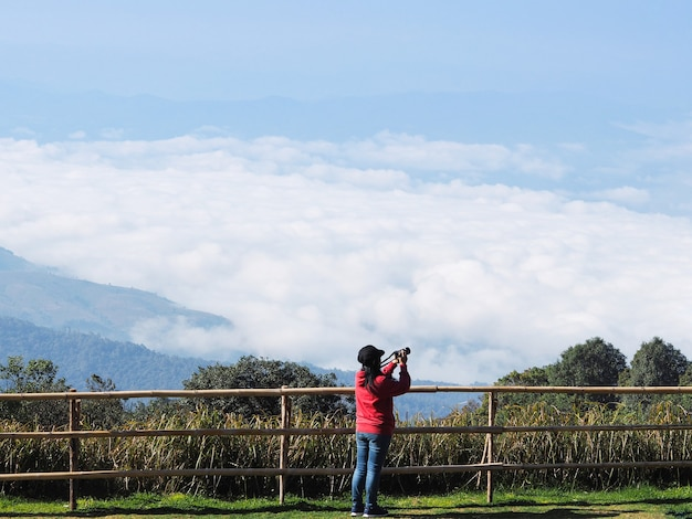Back view of asian woman holding camera taking photograph the fog over high mountain at chiangmai