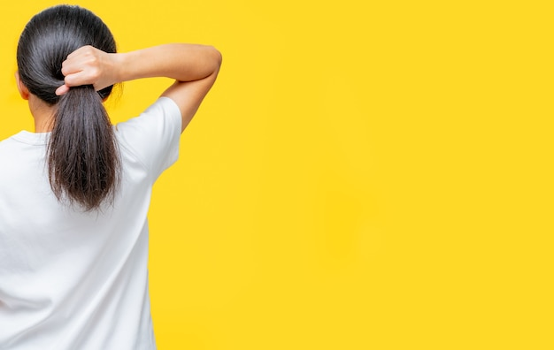 Back view of asian woman holding damaged hair on yellow background with copy space. split ends hair problem in woman. dry and brittle black long hair needs shampoo and conditioner for spa treatment.