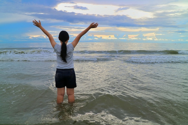 Back view of asian woman raise hands with the sea, wave beat, colorful sky.