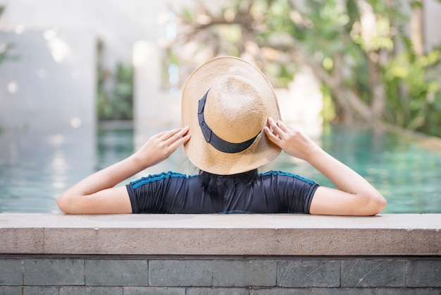 Back view of asian woman with hat relaxing