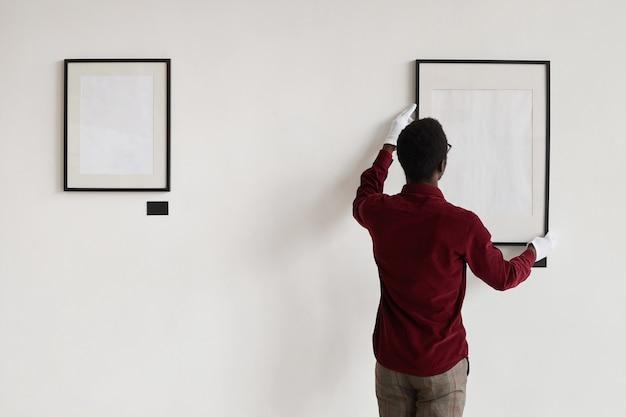 아트 갤러리 또는 전시회를 계획하는 동안 벽에 빈 프레임을 걸려 아프리카 계 미국인 남자의 뒷면,