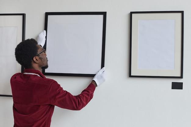 아트 갤러리 나 전시회를 계획하는 동안 벽에 액자를 걸고있는 아프리카 계 미국인 남자의 뒷모습,