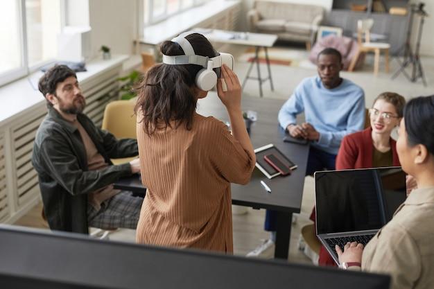 가상 현실 소프트웨어를 작업하는 다양한 it 개발 팀의 뒷모습, 사무실에서 vr 헤드셋을 착용한 젊은 여성에 초점