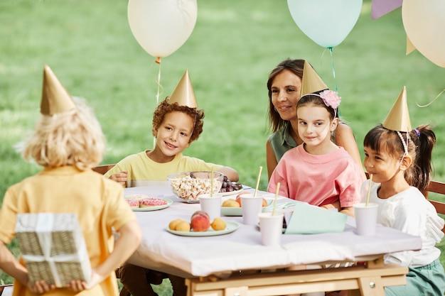 夏の屋外の誕生日パーティー中に贈り物を隠す小さな男の子の背面図