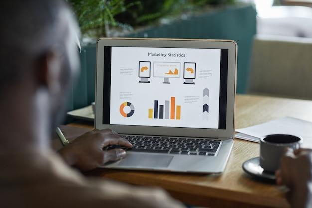 環境にやさしいインテリア、コピースペースのカフェテーブルで作業しながらグラフやチャートとラップトップを使用して現代のアフリカ系アメリカ人男性の背面図