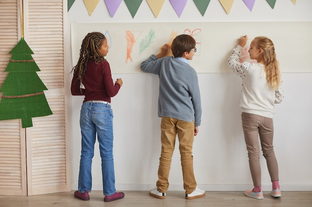 Вид сзади на многонациональную группу детей, рисующих на стенах, наслаждаясь уроком рисования в школе, скопируйте пространство