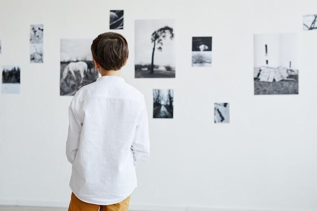 Вид сзади на мальчика, смотрящего на фотографии в галерее современного искусства, копией пространства
