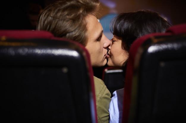 Вид сзади на молодая пара, целующаяся в кино, наслаждаясь романтическим свиданием, снято между сиденьями в темной комнате, копировальное пространство