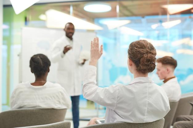 大学で医学セミナーを聴きながら手を挙げている若者の背面図、コピースペース