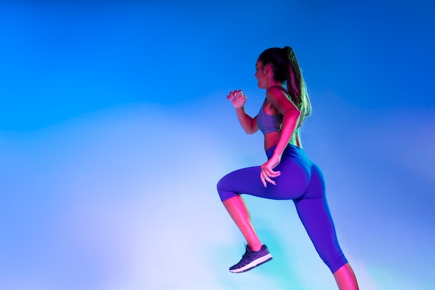 Back view of athlete running with blue background