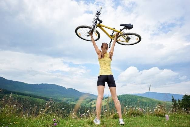 Back view of athlete woman biker holding yellow mountain bicycle above a head, standing on a grassy hill, enjoying summer day in the mountains. outdoor sport activity, lifestyle concept