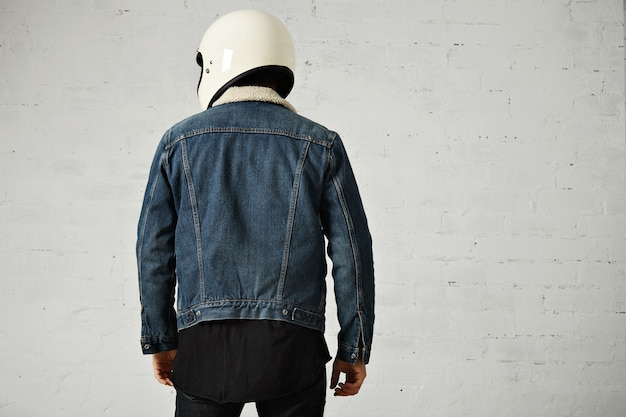 Vista posteriore del motociclista atletico che indossa giacca e casco in shearling denim club, isolato su bianco