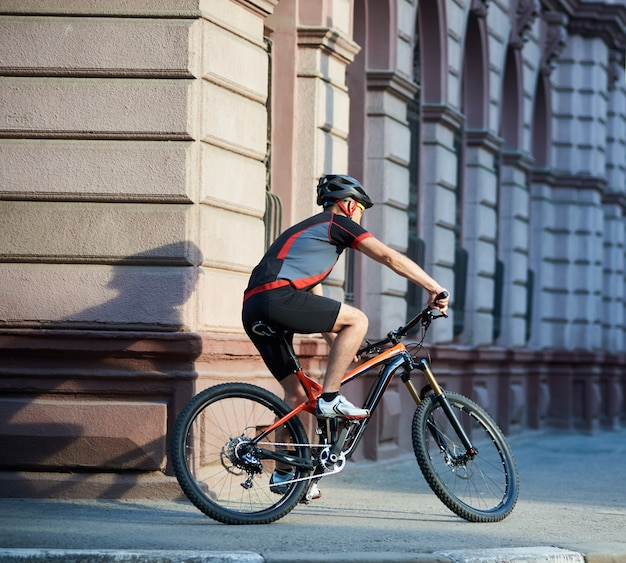 Back view of athletic cyclist riding bicycle in city center rushing and passing buildings. sportsman training, exercising outdoors. concept of healthy lifestyle