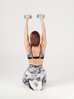 Back view of athletic woman holding up weights