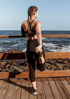 Vista posteriore della donna atletica che si estende sulla spiaggia