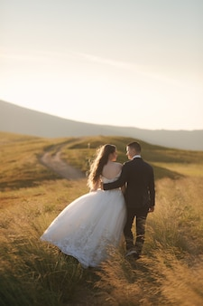 Back view of attractive bride and stylish groom enjoying romantic moments in the mountains at sunset