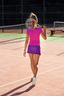 Back view of attractive female tennis player in uniform with tennis racket walking on the outdoor tennis court