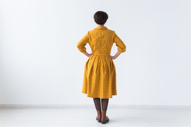 Back view of attractive woman in a yellow dress posing on white room with copyspace