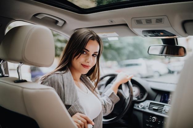 Vista posteriore di una giovane donna attraente di affari che osserva sopra la sua spalla mentre guida un'auto