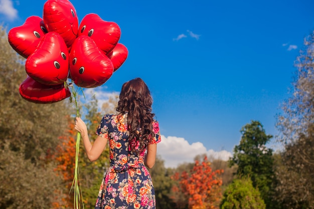 Back view of attractive young girl with red smiling balloons in hand outdoor