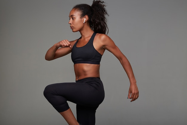 Back view of attractive young slim dark skinned curly brunette woman with casual hairstyle doing physical exercises indoor, posing in sporty clothes