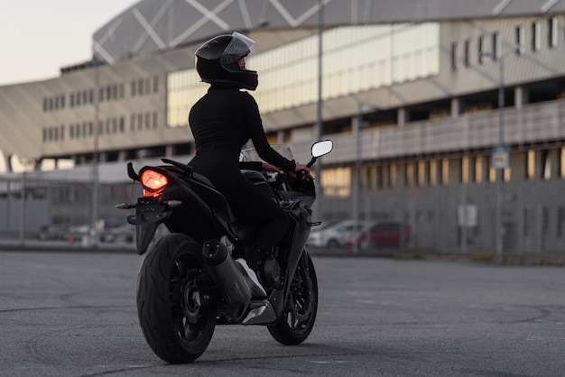 Back view of attractive young woman in black tight-fitting suit and full-face protective helmet rides on sports motorcycle at urban outdoors parking in the evening.
