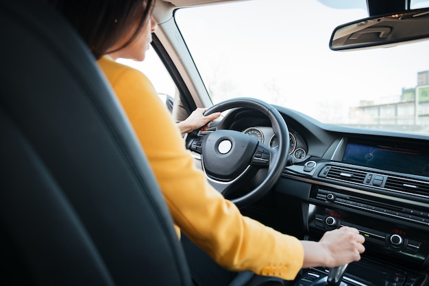 Back view of attractive young woman looking on the road while driving a car