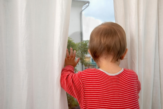 Back view of baby in red striped romper looking out of window leaning with hands on glass