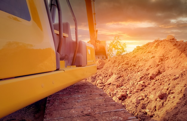 建設現場で土を掘って作業するバックホウの背面図。解体現場を掘るクローラーショベル。発掘機。土木設備。発掘車両。建設業。