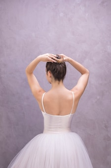 Back view ballerina fixing bun hairstyle