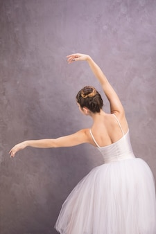 Back view ballerina posing with stucco background