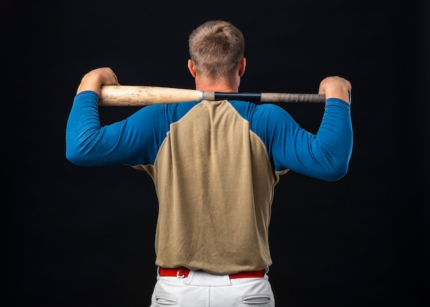 Back view of baseball player holding bat