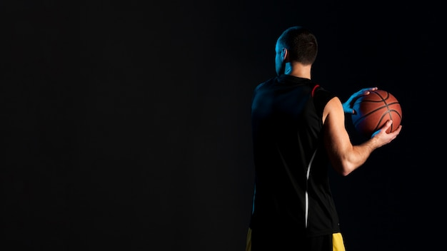 Back view of basketball player with ball and copy space