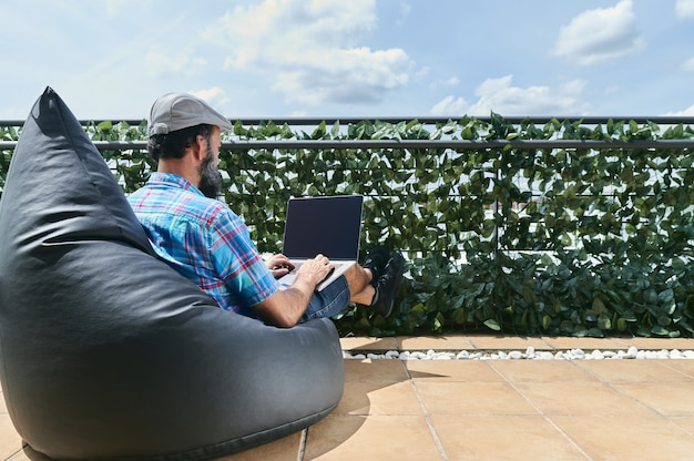 Back view of bearded man working with his laptop on the terrace of his house on a sunny day