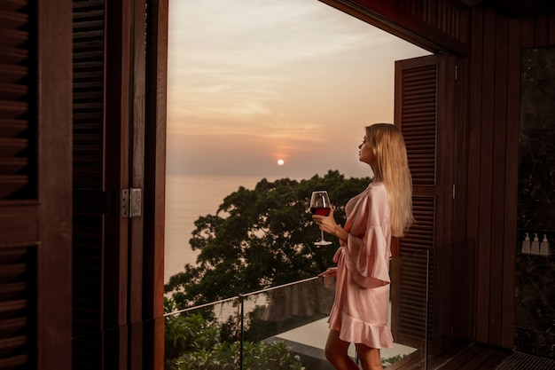 Back view: beautiful blonde woman in pink bathrobe enjoying a glass of wine on the balcony. perfect sunset. relaxation concept