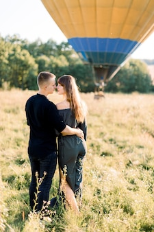 Back view of beautiful romantic couple in black stylish clothes, hugging each other, while standing in summer sunny field with hot air balloon