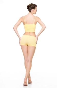Back view of a beautiful sporty female body in yellow underwear posing isolated on white wall