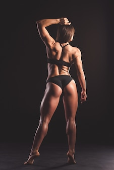 Back view of beautiful strong muscular woman.