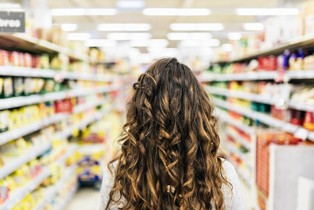 Back view of beautiful woman buying food in supermarket. market food concept.
