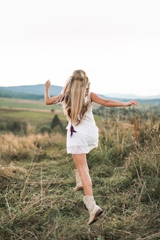 Back view of beautiful young boho woman in white dress at sunset in the summer field
