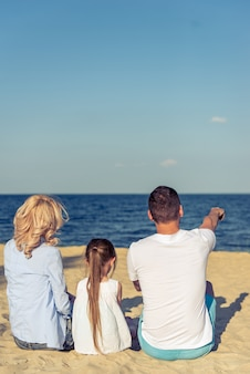 Back view of beautiful young couple with daughter on beach.